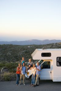 Multi-generation family relaxing in countryside on motor home vacation